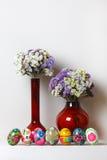Ovos da páscoa São em seguido Nos vasos vermelhos do fundo dois de tamanhos diferentes Nos vasos das flores Imagens de Stock