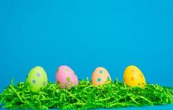 4 ovos da páscoa sortidos da cor em um fundo azul Fotografia de Stock Royalty Free