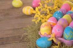 Ovos da páscoa tingidos por crianças ainda na vida rústica com as flores amarelas da mola Fotografia de Stock Royalty Free
