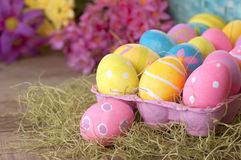 Ovos da páscoa tingidos por crianças ainda na vida rústica com as flores coloridas da mola Foto de Stock