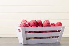 Ovos da páscoa vermelhos em um recipiente de madeira Fotos de Stock Royalty Free