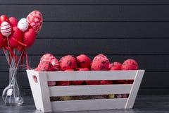 Ovos da páscoa vermelhos em um recipiente de madeira Imagem de Stock