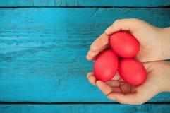 Ovos da páscoa vermelhos nas mãos Imagem de Stock