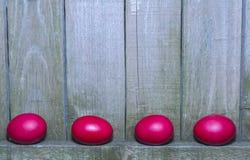 Ovos da páscoa vermelhos no fundo de madeira rústico da cerca Imagens de Stock