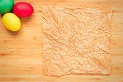 Ovos da páscoa vermelhos, verdes, amarelos em um fundo de madeira claro Ovo Imagens de Stock