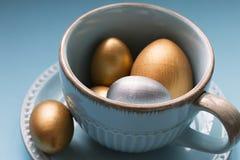 Ovos da p?scoa do ouro e da prata em uma caneca da porcelana em um fundo azul Fim acima Vista lateral foto de stock