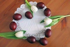 Ovos da p?scoa e tulipas brancas na tabela apresentada na forma de um cora??o foto de stock royalty free
