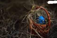 Ovos da p?scoa em uma cesta em um feno com um fundo borrado imagens de stock royalty free