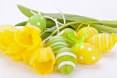 Ovos da páscoa amarelos e verdes coloridos da mola Foto de Stock