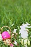 Ovos da páscoa coloridos, coelho de madeira e flores na grama fresca da mola no jardim Fotografia de Stock