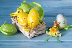 Ovos da páscoa coloridos em uma estatueta da cesta e do coelho no fundo de madeira azul Fotografia de Stock