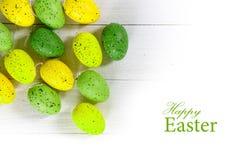 Ovos da páscoa verdes e amarelos na madeira branca, parte traseira isolada do canto Fotos de Stock Royalty Free