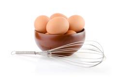 Ovos de Brown em uma bacia com batedor de ovos Fotos de Stock