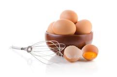 Ovos de Brown em uma bacia com batedor de ovos Fotografia de Stock