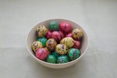 Ovos de codorniz coloridos em uma bacia no fundo da tela Foto de Stock Royalty Free