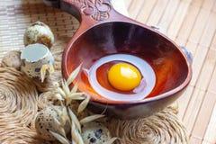 Ovos de codorniz crus frescos na colher de madeira na palha r?stica e no fundo de madeira do vintage imagens de stock
