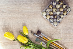 Ovos de codorniz e tulipas amarelas com pincéis em um backg de madeira Imagens de Stock