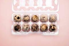 Ovos de codorniz em uma caixa plástica do ovo sobre imagens de stock royalty free