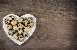 Ovos de codorniz em uma placa dada fôrma coração Imagem de Stock