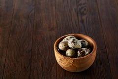 Ovos de codorniz frescos em uma bacia de madeira em um fundo de madeira escuro, vista superior, close-up foto de stock