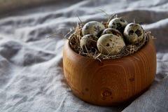 Ovos de codorniz frescos em uma bacia de madeira em um fundo de madeira escuro, vista superior, close-up imagens de stock