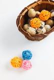 Ovos de codorniz isolados em uma cesta com as bolas de madeira decorativas Imagem de Stock Royalty Free