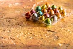 Ovos de cores diferentes, ovos de codorniz no fundo alaranjado Conceito feliz de Easter Alimento saudável da Páscoa Copie o espaç Imagem de Stock