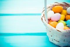 Ovos de doces coloridos da Páscoa na cesta branca no fundo da madeira de turquesa Copyspace foto de stock royalty free