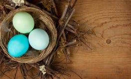 Ovos de Easter em um ninho em um fundo de madeira Fotografia de Stock Royalty Free
