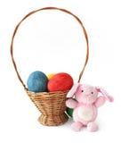 Ovos de Easter pintados e um coelho em uma cesta Imagens de Stock