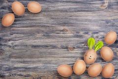 Ovos de Hen's no fundo de madeira natural Um ovo tem a cara engraçada e as orelhas do coelhinho da Páscoa feitas das folhas da  foto de stock royalty free