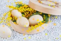 Ovos de madeira da Páscoa com uma mimosa imagem de stock royalty free