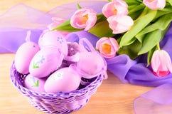 Ovos decorativos da Páscoa na cesta e nas tulipas Fotos de Stock Royalty Free