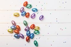 Ovos do chocolate da Páscoa mini envolvidos na folha colorida, dispersada em um fundo de madeira branco, vista superior, espaço d Fotos de Stock
