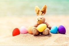 Ovos do coelhinho da Páscoa e da cor na areia da praia imagem de stock royalty free