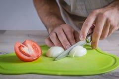 Ovos do corte na placa de corte verde Imagem de Stock