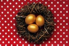 Ovos dourados da Páscoa feliz no ninho no fundo de às bolinhas vermelhos Imagens de Stock Royalty Free