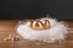 Ovos dourados no ninho e moedas na tabela de madeira Fotos de Stock