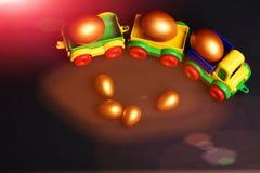 Ovos dourados tradicionais no brinquedo ou na locomotiva colorida plástica do carro Foto de Stock Royalty Free