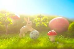 Ovos e coelhos de Easter Conceito da natureza do feriado com caça de easter Ovos no prado ensolarado Imagem de Stock
