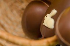 Ovos e doces do coelhinho da Páscoa do chocolate na cesta da Páscoa Imagem de Stock