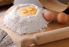 Ovos e farinha na placa de estaca Fotografia de Stock Royalty Free