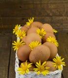 Ovos e margaridas amarelas em uma cesta no fundo de madeira áspero Foto de Stock
