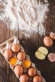 Ovos e ovos quebrados no pacote em um fundo de madeira Era a farinha dispersada em uma tabela de madeira Imagens de Stock