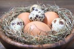 Ovos e palha em uma bacia de madeira Foto de Stock