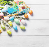 Ovos e pintura coloridos em uma tabela de madeira branca Fotografia de Stock