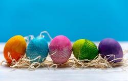 Ovos em todas as cores do arco-íris em seguido em um brilhante, fundo da mola imagem de stock royalty free