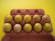 Ovos em um pacote em um fundo amarelo, isolado Imagem de Stock