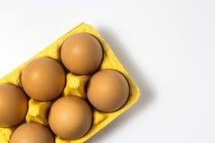 Ovos em um pacote em um fundo branco Imagem de Stock