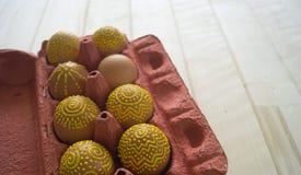 Ovos em um pacote em um fundo de madeira, isolado Os testes padrões amarelos são pintados Fotos de Stock Royalty Free